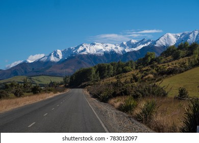 Empty road leading towards snow-capped mountains