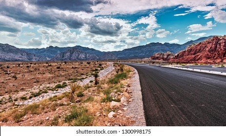 An empty road in the middle of Red Rock Canyon Desert near Las Vegas, completely vacant, rumbling storm overhead as clouds form over the dark mountains in the distance.
