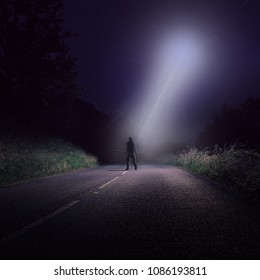 An empty road at night with a lone figure looking up at bright UFO with a white beam of light coming down