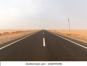 an empty road on the dessert in Egypt. Sand overall, road in the middle with an Egyptian flag on the right site.