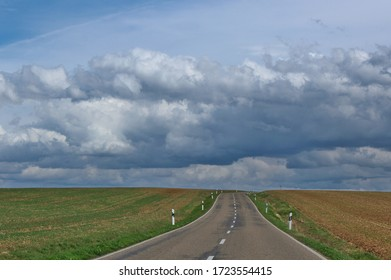 An empty road passing between fields with dramatic clouds in the sky overhead in Bavaria, Germany