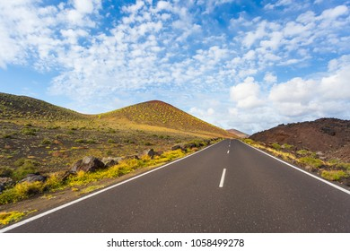 Empty road running towards the mountains with blue, cloudy sky and green plants. Lanzarote, Spain, Europe.