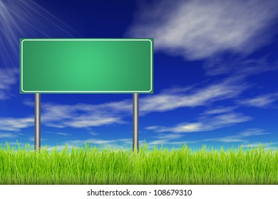 Empty road sign in a green summer grass over a blue sky background