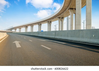 Empty road surface floor with city overpass viaduct bridge in sh