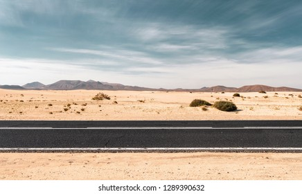 Empty road through the desert dunes with copy space