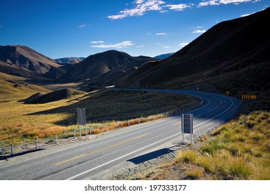 Empty road through mountains in New Zealand on a sunny summer morning.