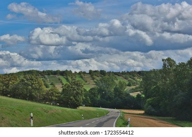 An empty road winding around a hill, with trees and fields in the distance and clouds in the sky, in Bavaria, Germany