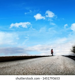 empty road and young adult woman on countryside landscape