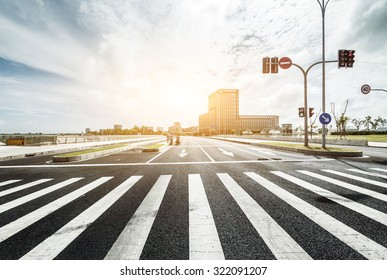 empty road with zebra crossing and direction board in modern city under sunlight