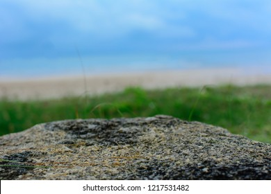 Empty rock table over blurred grass beach sea and sky. Can used for table for put products.