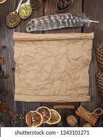 empty rolled brown paper sheet on a wooden background in the middle of spices for making mulled wine, empty space