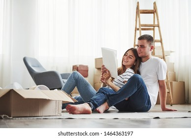 Empty room with boxes and ladder. Cheerful young couple in their new apartment. Conception of moving.