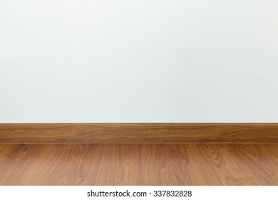 empty room with brown wood laminate floor and white mortar wall background
