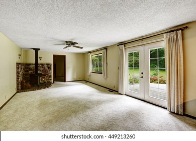 Empty room with carpet floor and fireplace. View to backyard