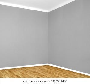empty room corner with wooden floor and grey wall