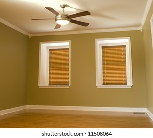 Empty room with dormer windows, hardwood flooring and moldings.