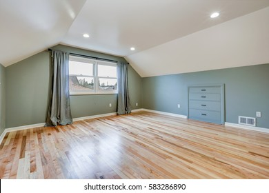 Empty room features green walls paint color , white vaulted ceiling over light hardwood floor. Northwest, USA