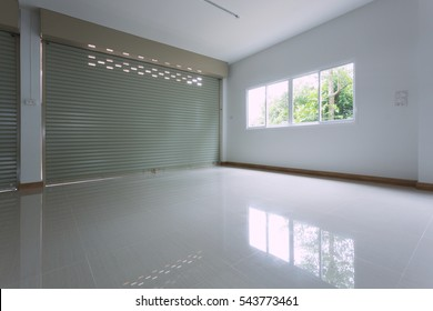 empty room in house residential building with aluminium roller shutter door and window glass sliding and white flooring tile