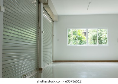 empty room in house residential building with aluminium roller shutter door closed and glass window sliding and white flooring tile