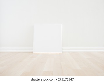 Empty room interior with blank artwork picture frame standing on wooden floor. Bright white scandinavian design and clean contemporary architecture. The room works as backdrop for a new home.