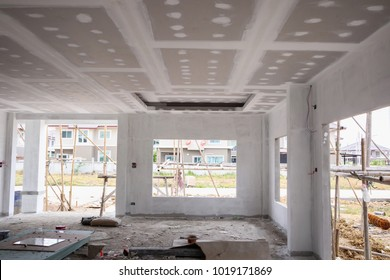 Empty room interior with gypsum board ceiling at house construction site