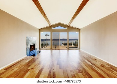 Empty room interior with hardwood floor, vaulted ceiling and fireplace with tile trim. Glass doors leading to the balcony
