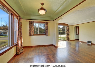 Empty room interior of tudor style home with colorful window curtains and hardwood floor. Northwest, USA