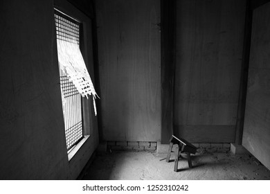 An empty room with a single stool. The wind is blowing the tattered curtains. The black and white scene is suitable to illustrate simplicity, loneliness, desolation, or destruction.