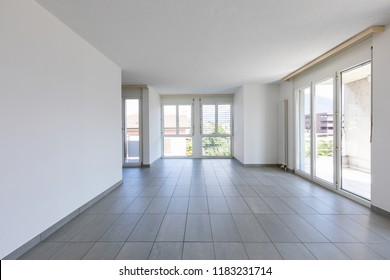 Empty room with tiles and large, bright windows. Nobody inside