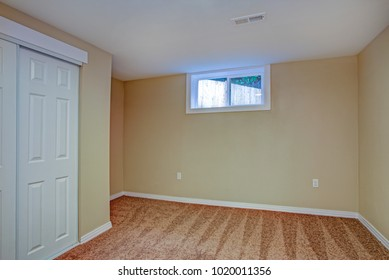 Empty room with white doors closet, sand beige walls, carpet floor in a luxury home.