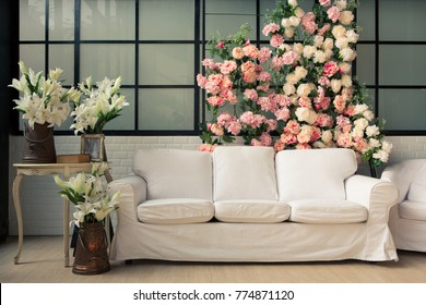 empty room with white sofa beautiful interior with soft warm sun light in vintage environment style with many flowers and vase