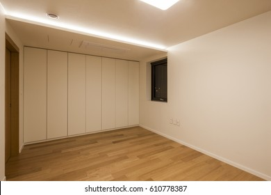 Empty room with white wardrobe(closet), wood floor, lighting.