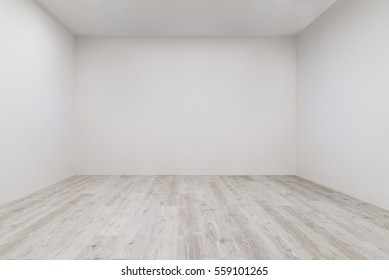 Empty room with whitewashed floating laminate flooring and newly painted white wall in background