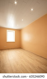 Empty room with window and turned on lights on the ceiling. New renovated apartment