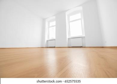 empty room, wooden floor in new apartment, blurred