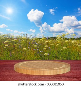 Empty round cutting board on wooden table.In the background blurred beautiful field with wild flowers