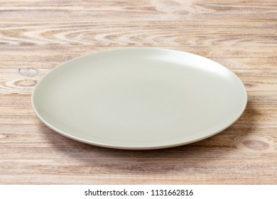 empty round plate for food on wood bachground. Perspective view.