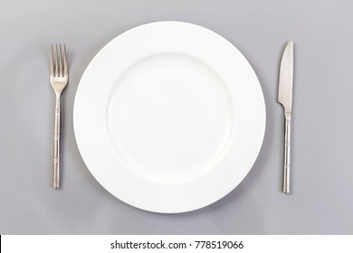 Empty Round Plate with Fork and Knife Top View Isolated on slate Background.