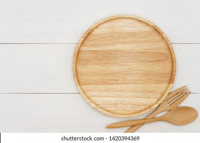 Empty round wooden plate with spoon and fork on white wooden table. Top view image.