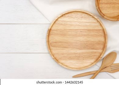 Empty round wooden plate with spoon, fork and white tablecloth on white wooden table. Top view image.