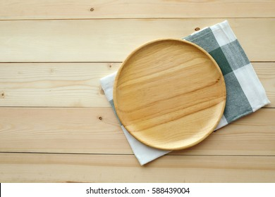 Empty round wooden tray and napkin on table, top view, flat lay, food display montage background with copy space