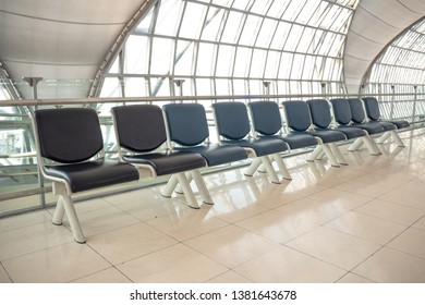 Empty row of black seat for waiting at the gate in the airport