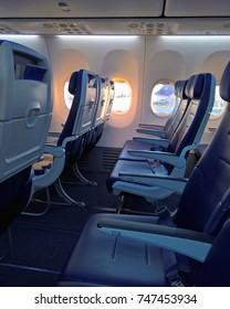 Empty row of seats on a narrow body jet airliner, sunrise