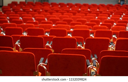Empty rows of chair in a conference / theatre / Cinema hall. Empty red seats