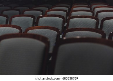 Empty Rows of Padded Wooden Chairs with Dim Soft Light in Auditorium or Theatre