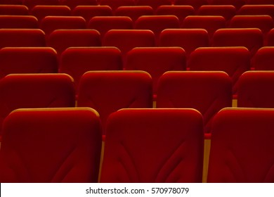Empty rows of red chairs without people in cinema or concert hall
