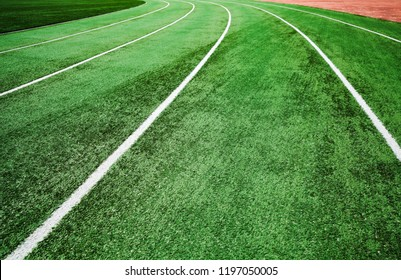 Empty running track with bright green artificial turf and white lines