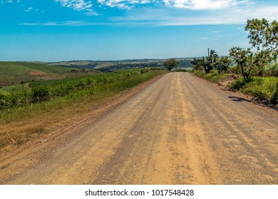 Empty rural farm dirt road leading through trees and sugar cane plantations against blue cloudy sky landscape in South Africa