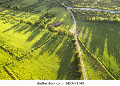 Empty rural road across green farming fields with grazing sheep Top down aerial shoot in Shropshire, United Kingdom
