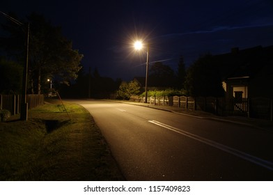 Empty rural road fragment with lamp at night